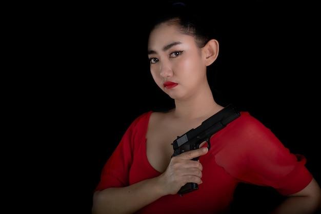Retrato de uma bela mulher asiática usando um vestido vermelho com uma das mãos segurando uma pistola 11m