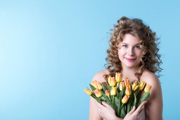 Retrato de uma bela mulher caucasiana sorridente com tulipas em estúdio em um fundo azul. rosto feminino feliz, dia da mulher.