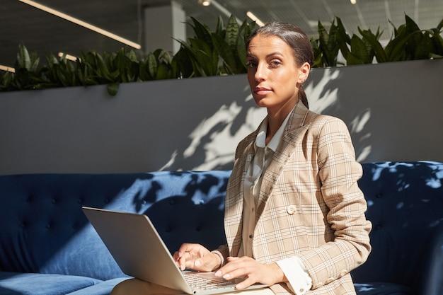 Retrato de uma bela mulher de negócios mestiça enquanto usa o laptop na luz do sol, copie o espaço