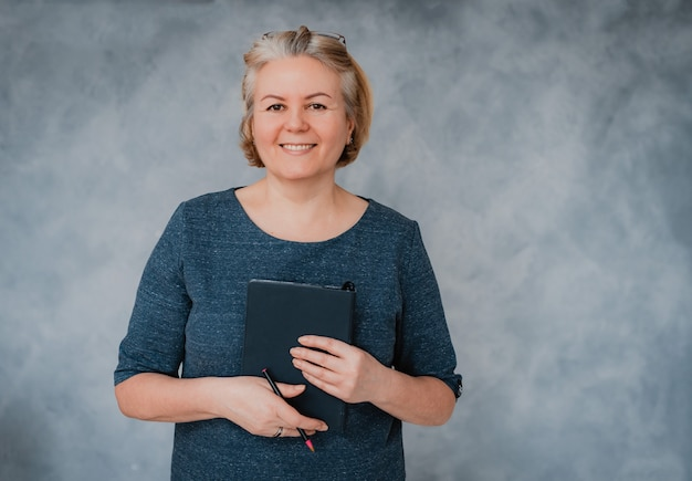 Retrato de uma bela mulher de negócios sênior em uma parede cinza