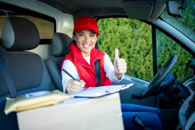 Retrato de uma bela mulher entregador ou mensageiro sentado em sua van aparecendo os polegares.