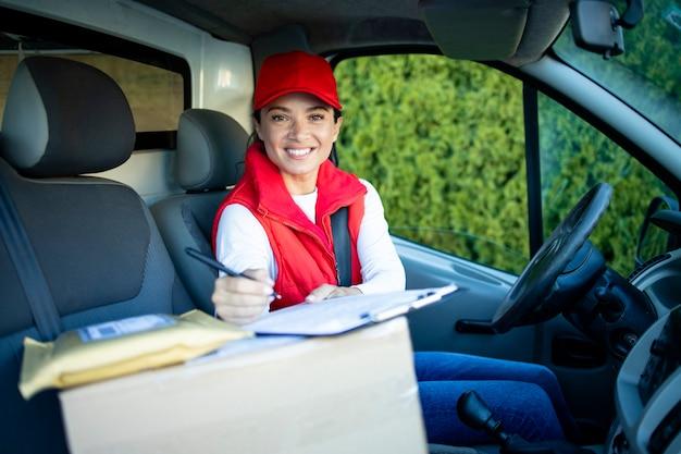 Retrato de uma bela mulher entregador ou mensageiro sentado em sua van com os pacotes.