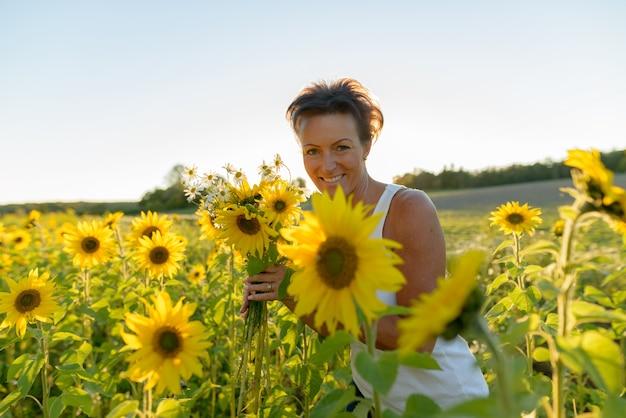 Retrato de uma bela mulher escandinava madura no campo de girassóis florescendo ao ar livre