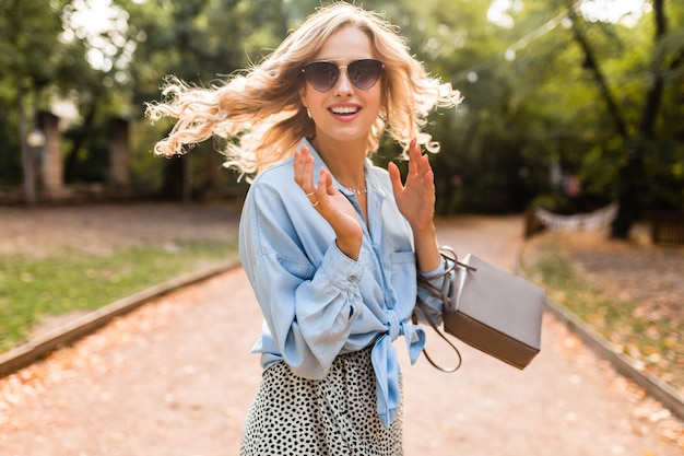 Retrato de uma bela mulher loira sorridente caminhando no parque em um dia de verão brilhante em uma camisa azul elegante usando óculos escuros e bolsa, estilo de moda de rua, rindo de bom humor