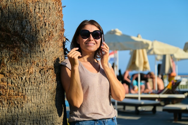 Retrato de uma bela mulher madura sorridente relaxante no hotel resort, mulher em óculos de sol em pé perto de uma palmeira usando smartphone, copie o espaço. férias, verão, turismo, resort, pessoas de meia-idade