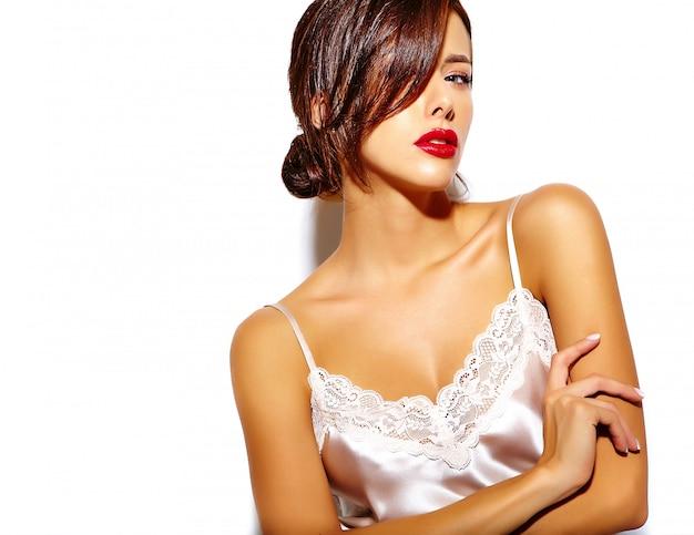 Retrato de uma bela mulher morena sexy com os lábios vermelhos em lingerie de pijama no fundo branco