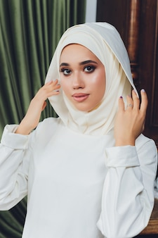 Retrato de uma bela mulher muçulmana em roupas islâmicas tradicionais e cobrindo a cabeça