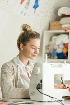 Retrato de uma bela mulher na máquina de costura