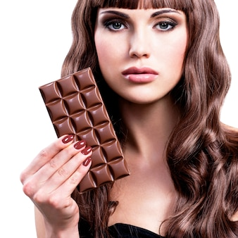 Retrato de uma bela mulher sexy com barra de chocolate - isolado no branco.