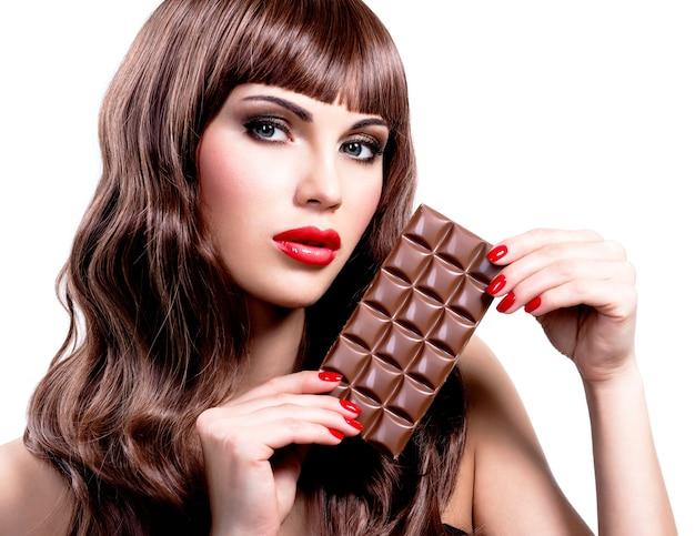 Retrato de uma bela mulher sexy com barra de chocolate. rosto de closeup com maquiagem brilhante, isolado no branco.