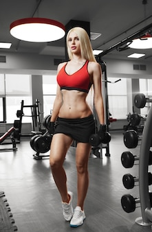 Retrato de uma bela mulher sexy, vestida com roupas esportivas na academia