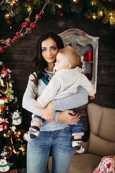 Retrato de uma bela mulher sorridente com penteado e maquiagem segurando seu lindo bebê contra a árvore de natal decorada