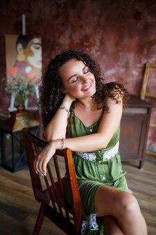 Retrato de uma bela mulher sorridente de aparência europeia em um vestido com penteado de cachos. moda e beleza