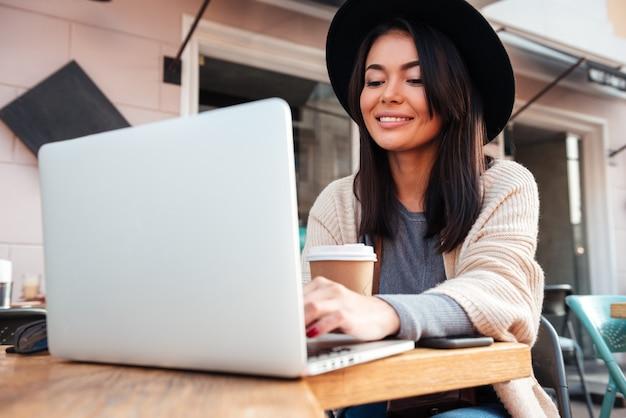 Retrato de uma bela mulher sorridente digitando no laptop