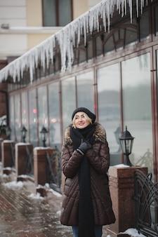 Retrato de uma bela mulher sorridente feliz posando ao ar livre no inverno.