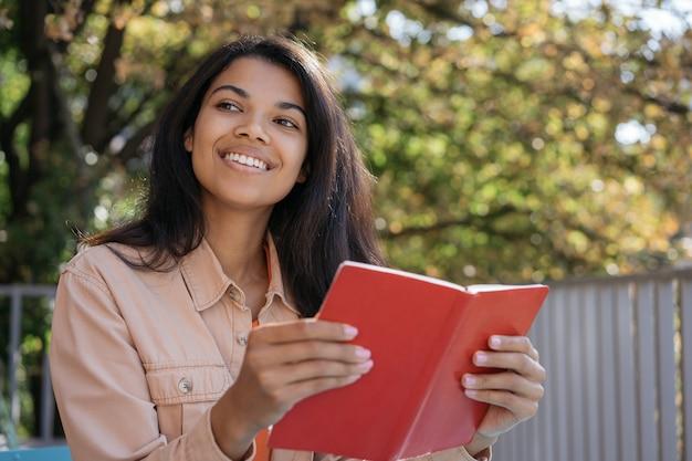 Retrato de uma bela mulher sorridente lendo livro, estudando, aprendendo línguas, sentado no parque