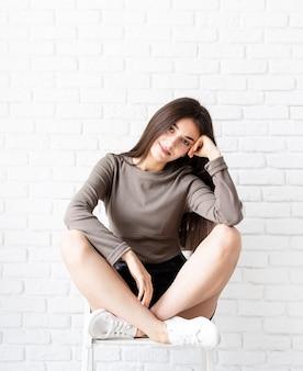 Retrato de uma bela mulher sorridente morena com cabelos longos, vestindo uma camisa marrom e shorts de couro preto sentado no fundo da parede de tijolo