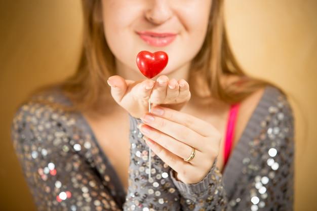 Retrato de uma bela mulher sorridente segurando um coração vermelho decorativo na mão