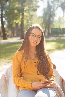 Retrato de uma bela mulher sorridente usando óculos e segurando um smartphone enquanto está sentado no parque
