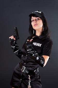 Retrato de uma bela policial sexy com algemas em um uniforme preto que aponta uma arma. isolado em preto.