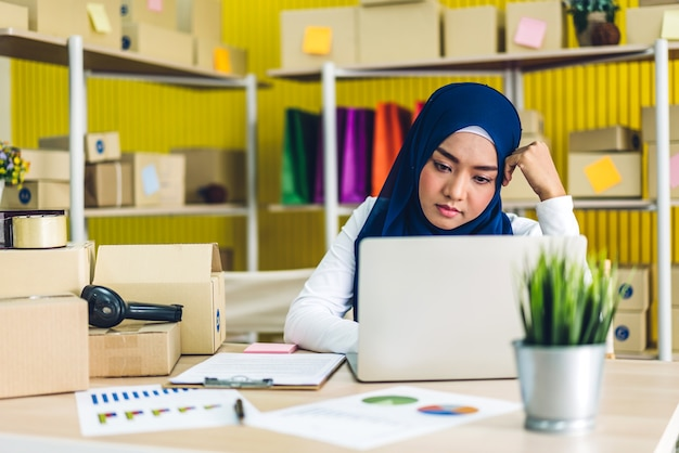 Retrato de uma bela proprietária muçulmana, mulher asiática freelancer sme negócios on-line, compras trabalhando em um computador laptop com a caixa de pacotes na mesa em casa - negócios on-line de envio e entrega