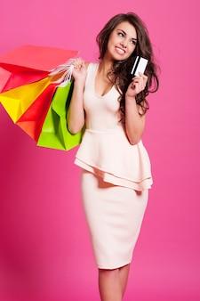 Retrato de uma bela shopaholic com sacolas de compras e cartão de crédito