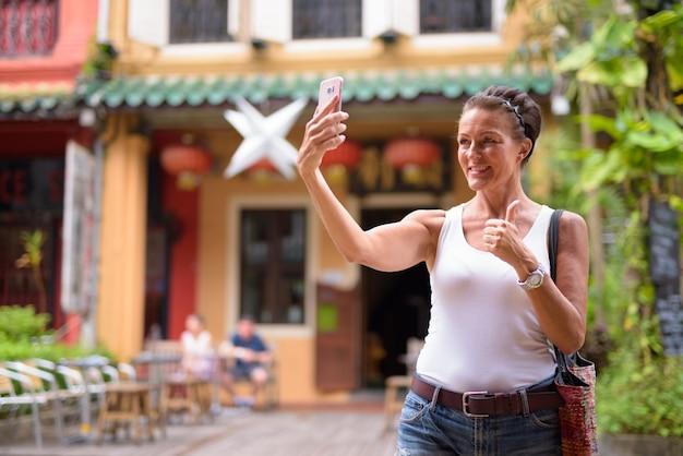Retrato de uma bela turista madura curtindo a vida enquanto viaja na cidade de cingapura