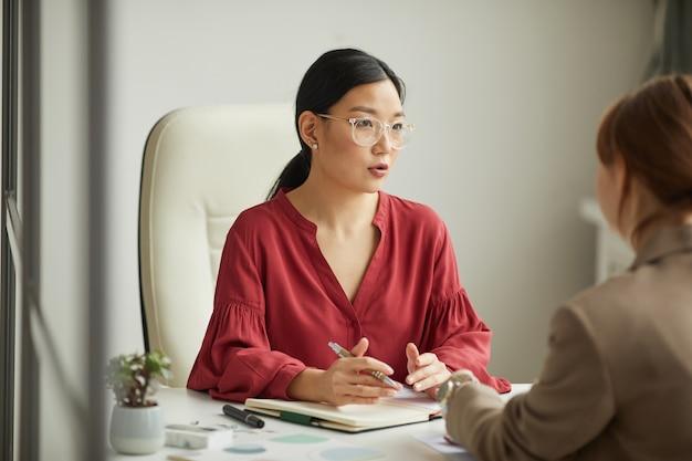 Retrato de uma bem-sucedida empresária asiática falando com o cliente enquanto trabalha na mesa em um cubículo de escritório branco, copie o espaço