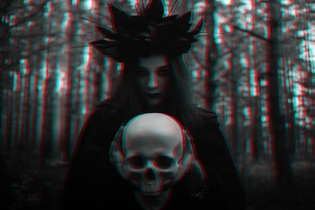 Retrato de uma bruxa terrível com uma caveira nas mãos de um homem morto realiza um ritual místico oculto
