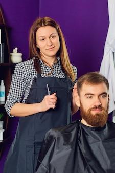 Retrato de uma cabeleireira em salão de beleza dentro de casa.