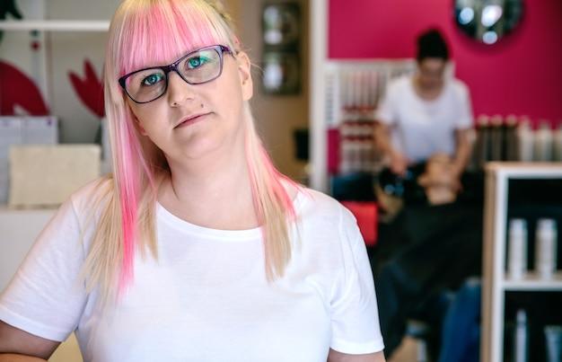 Retrato de uma cabeleireira em um salão de cabeleireiro e beleza com uma funcionária lavando o cabelo de uma mulher ao fundo