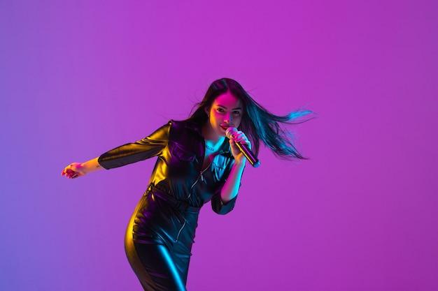 Retrato de uma cantora caucasiana isolado no fundo roxo do estúdio em luz de néon