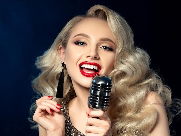 Retrato de uma cantora loira e bonita segurando um microfone de estilo retrô. bela maquiagem com lábios vermelhos. concerto, karaokê, celebridade, show musical ou conceito de clube noturno.