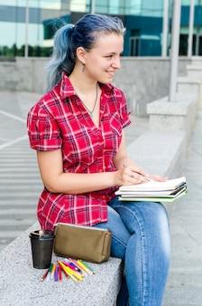 Retrato de uma casual fofa e jovem garota com cabelo azul em jeans no verão urbano desenhando ou escrevendo algo em um notebook