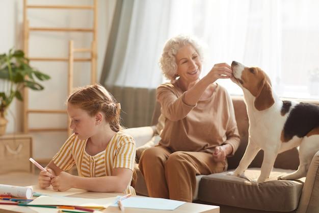 Retrato de uma cena familiar tranquila com uma mulher sênior brincando com um cachorro e uma linda garota ruiva tirando fotos ao lado dela no interior de uma casa aconchegante
