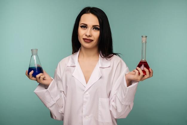 Retrato de uma cientista examinando frascos com diferentes produtos químicos em laboratório médico