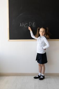 Retrato de uma colegial com tranças, aprendendo o alfabeto
