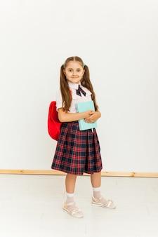Retrato de uma colegial de uniforme em pé no fundo branco
