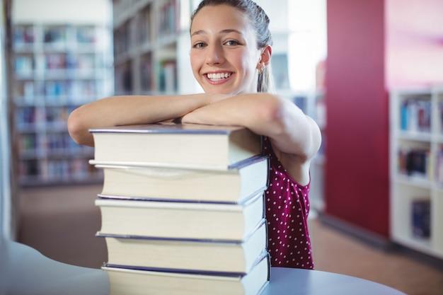 Retrato de uma colegial feliz inclinando-se sobre livros empilhados na biblioteca