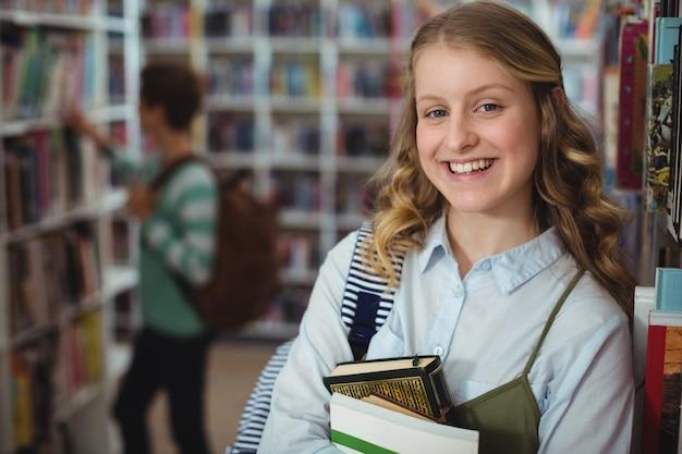 Retrato de uma colegial feliz segurando livros na biblioteca