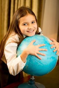 Retrato de uma colegial fofa segurando um grande globo terrestre