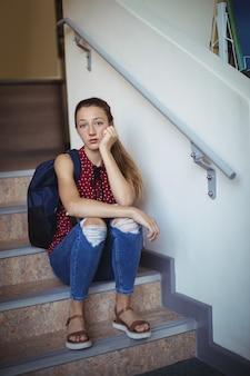 Retrato de uma colegial triste sentada sozinha na escada