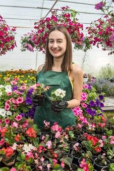 Retrato de uma creche feminina que trabalha com flores na bela e brilhante estufa em um dia ensolarado
