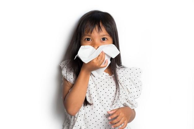 Retrato de uma criança asiática doente limpando e limpando o nariz com um lenço de papel