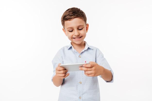 Retrato de uma criança bonitinha jogando jogos no smartphone