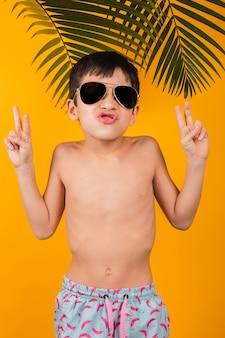 Retrato de uma criança brincalhona usando óculos escuros e fazendo o sinal v