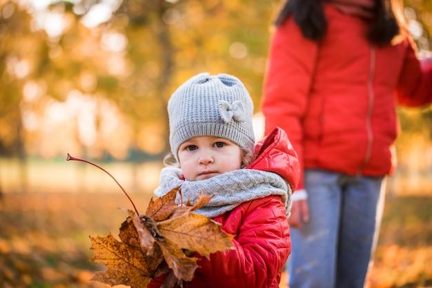 Retrato de uma criança brincando com uma folha no parque outono