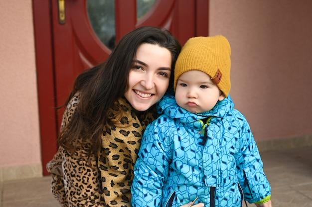 Retrato de uma criança carrancuda e uma mãe alegre. criança mal-humorada na rua.