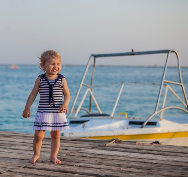 Retrato de uma criança com olhos golubymi no cais do barco. verão, felicidade, mar, oceano