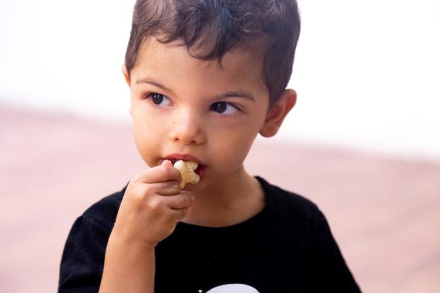 Retrato de uma criança comendo uma batata frita com uma expressão ausente enquanto olha para o lado